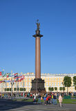 Alexander column on Palace square, covered with natural lawn of green grass and trees on a Sunny day on the background of flags Royalty Free Stock Images