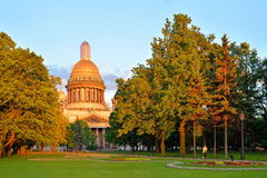 Alexander garden and sunlit St. Isaac's Cathedral at sunset in S. Aint-Petersburg Stock Images