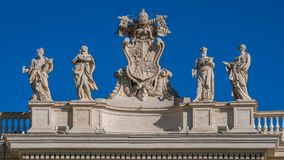 Alexander VII coat of arms and saints statues Mark, Mary, Ephraim and Theodosia in the colonnade of Saint Peter Basilica in Rome stock photo