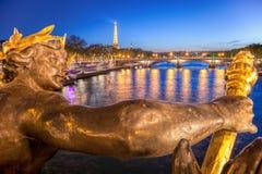 Alexandre III bro mot Eiffeltorn på natten i Paris, Frankrike Royaltyfri Foto