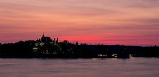 Alexandria Bay Sunset över hjärtaön med den Boldt slotten arkivfoto