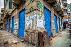 11.16.2018 Alexandria, Egypt, Kind of a corner of an old house with bright and blue doors flooded with old advertisements. On a cloudy day royalty free stock image