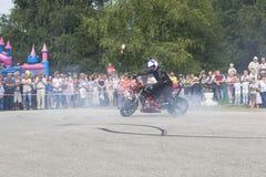Alexei Kalinin drar på asfaltgummihjul av hans motorcykel arkivfoto