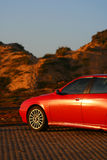 Alfa Romeo on the beach in Portugal. Red beautiful car on the sunset, Portugal stock images