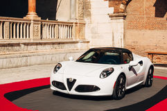 Alfa Romeo 4C in Verona. Verona, Italy - September 22, 2016: White Alfa Romeo 4C car on Piazza Dante in Verona, in preparation for The Red Table event. The event Royalty Free Stock Photography