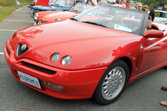 Alfa romeo spider in a row of cars. Red 1990s Alfa Romeo spider sports car parked in a row next to other classic Alfa Romeo cars and people. Outdoors in the Stock Photos