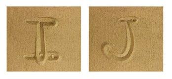 Alfabet I-J på sand Royaltyfri Bild