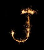 Alfabet J (versalar) för tomteblossfyrverkeriljus på natten Royaltyfria Bilder