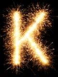 Alfabet K för tomteblossfyrverkeriljus på svart Royaltyfri Fotografi
