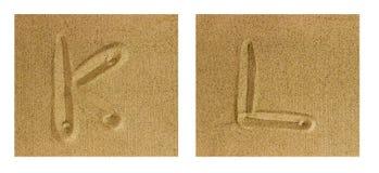 Alfabet K-L på sand Arkivfoton