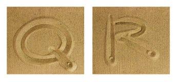 Alfabet Q-R på sand Arkivbild
