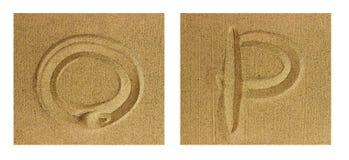 Alfabet som ÄR O-P på sand Royaltyfri Foto
