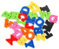 Alfabet som är skriftligt i mångfärgade plast-ungebokstäver Arkivbild