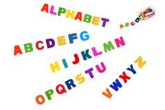 Alfabet som är skriftligt i mångfärgade plast-ungebokstäver och colorf Fotografering för Bildbyråer