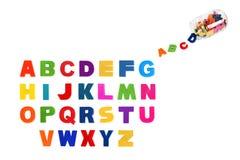 Alfabet som är skriftligt i mångfärgade plast-ungebokstäver och colorf Royaltyfri Fotografi