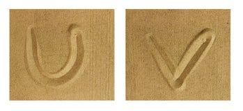 Alfabet som ÄR U-V på sand arkivbild
