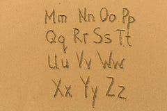 Alfabet som dras på sanden av en strand Fotografering för Bildbyråer