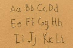 Alfabet som dras på sanden av en strand Royaltyfri Foto