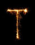 Alfabet T (versalar) för tomteblossfyrverkeriljus på natten Royaltyfri Fotografi