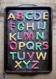 Alfabet in verfraaide kleurrijke koekjes op bakseldienblad Royalty-vrije Stock Foto