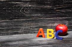 Alfabetbokstäver och rött äpple på en svart bakgrund arkivfoto