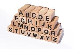 Alfabetbokstäver på träkuber på vit bakgrund Arkivbild
