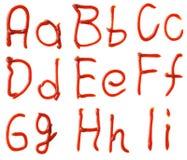 Alfabetbrieven van ketchupstroop die worden gemaakt. Stock Afbeeldingen