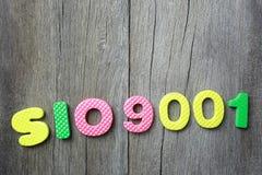 Alfabetet av ISO 9001 lägger på gammal brun wood golvbakgrund Arkivbilder