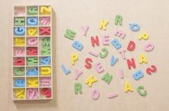 Alfabeti variopinti su carta marrone con la scatola di alfabeto Fotografie Stock Libere da Diritti
