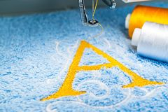 Alfabetlogodesign på handduken i beslag av broderimaskinen royaltyfria foton