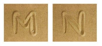 AlfabetM-N på sand Arkivfoton