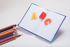 Alfabeto de ABC que aprende tema con el libro y los lápices Fotos de archivo libres de regalías