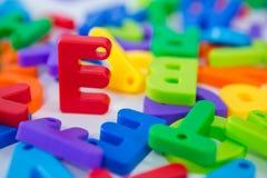 Alfabeto de E que se coloca entre el alfabeto del juguete Imagen de archivo libre de regalías