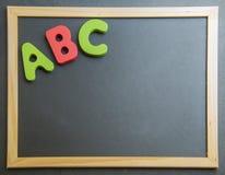 Alfabeto de madera colorido ABC en tablero negro Imágenes de archivo libres de regalías