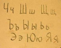 Alfabeto (del Ch a Ja) escrito en una playa de la arena Imágenes de archivo libres de regalías
