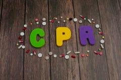 Alfabeto di colore nell'abbreviazione di parola CPR di rianimazione cardiopolmonare intorno alle pillole su fondo di legno fotografia stock libera da diritti
