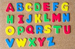 Alfabeto di legno variopinto della lettera maiuscola sul bordo del sughero Fotografia Stock