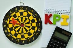 Alfabeto di legno variopinto KPI e calcolatore sulla nota del Libro Bianco immagine stock