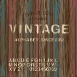 Alfabeto do selo do vintage e fundo de madeira Imagem de Stock