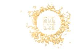 Alfabeto fatto delle lettere dei maccheroni isolate su fondo bianco w fotografia stock