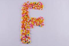Alfabeto feito de Sugar Coated Colorful Fennel Seeds fotografia de stock royalty free