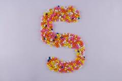 Alfabeto feito de Sugar Coated Colorful Fennel Seeds imagem de stock