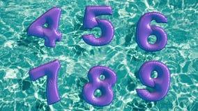 Alfabeto feito do anel inflável dado forma da nadada que flutua em uma piscina azul de refrescamento Imagens de Stock