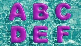 Alfabeto feito do anel inflável dado forma da nadada que flutua em uma piscina azul de refrescamento Foto de Stock Royalty Free