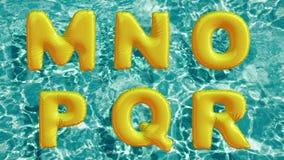 Alfabeto feito do anel inflável dado forma da nadada que flutua em uma piscina azul de refrescamento Foto de Stock
