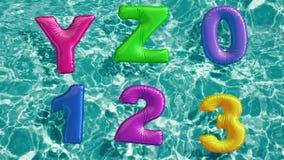 Alfabeto feito do anel inflável dado forma da nadada que flutua em uma piscina azul de refrescamento Fotos de Stock