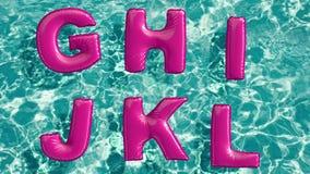 Alfabeto feito do anel inflável dado forma da nadada que flutua em uma piscina azul de refrescamento Imagem de Stock