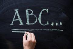Alfabeto femenino de la escritura de la mano en la pizarra negra Formación académica con las letras de ABC con el espacio de la c Fotografía de archivo
