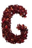 Alfabeto inglese Segni il G con lettere dai fiori secchi del tè dell'ibisco su un fondo bianco Lettere per le insegne, pubblicità Fotografie Stock
