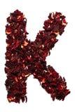 Alfabeto inglese Segni K con lettere dai fiori secchi del tè dell'ibisco su un fondo bianco Lettere per le insegne, pubblicità Fotografie Stock Libere da Diritti